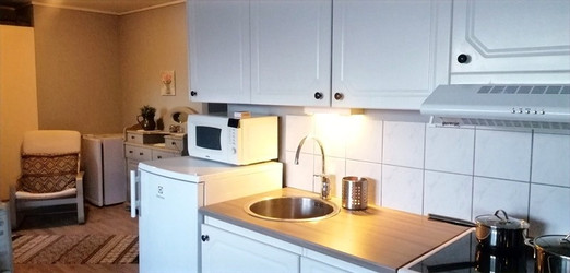 Kjøleskåp, mikrobølgeovn og fryseskåp inderst i hjørnet.