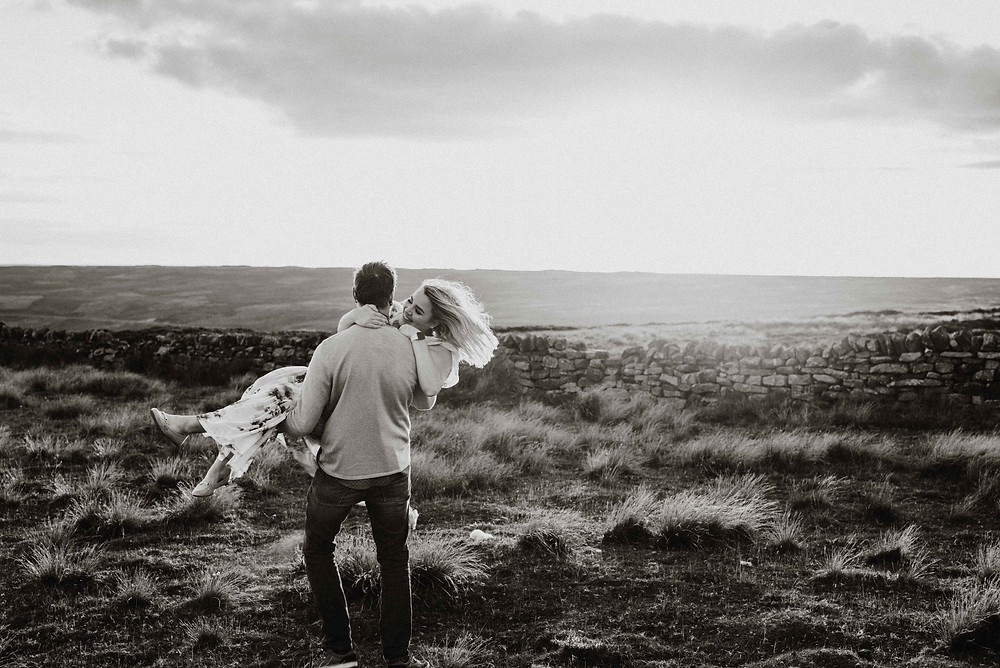 Engaged couple spinning in golden light on North York Moors
