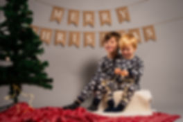 two brothers smile in front of christmas tree and bunting with light up star decorations