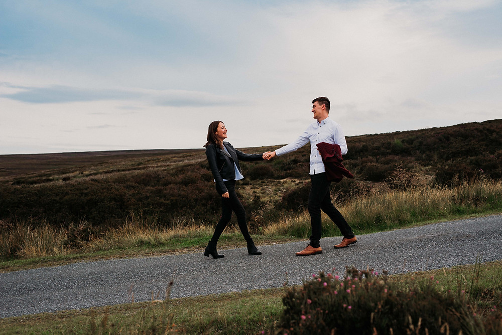 photo of couple walking along north york moors road