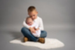 older brother holds baby sister close during studio portrait shoot