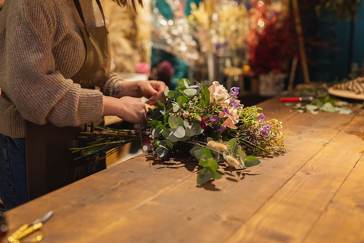 florist ties together real flower bouquet on wooden workbench in her shop