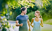 Photo of a man and woman jogging and looking at each other happily.