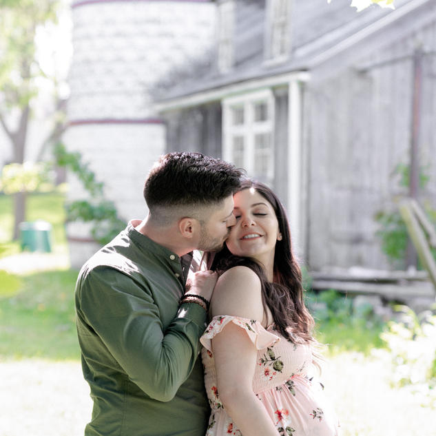Candid maternity photo of husband and wife kissing