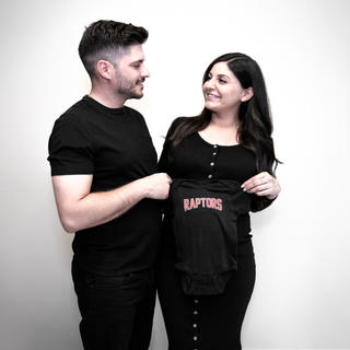 Candid maternity photo of husband and wife with Toronto Raptors onsie