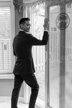 Groom posing by window in black and white