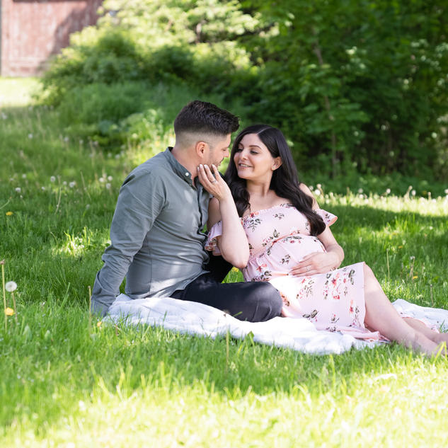 Candid  maternity photo of husband and wife sitting on blanket