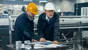 Two engineers discuss a blueprint while