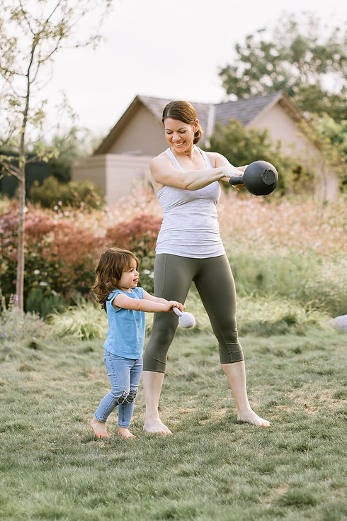 Postpartum woman swinging kettlebells with daughter