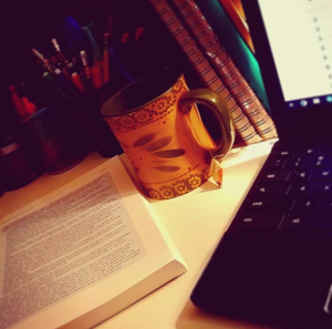 Photo of my desk while studying with laptop, textbook and cup of tea