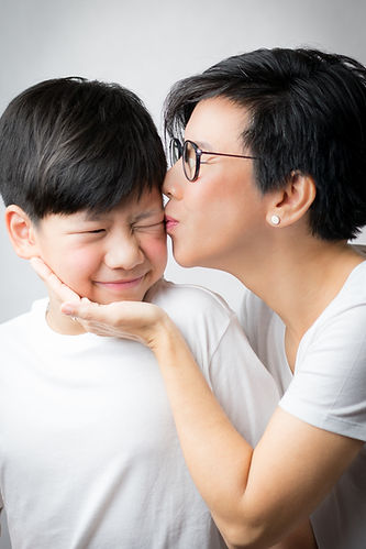 A smart looking asian mother gently kiss
