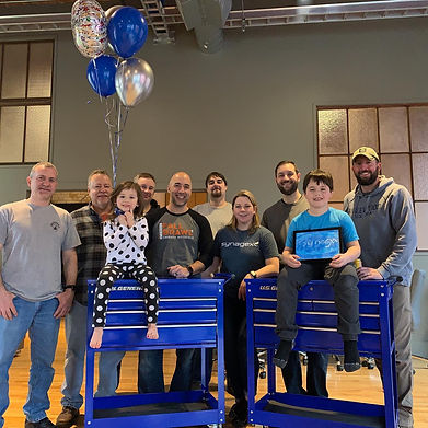 Synagex team photo with two children sitting on blue tool chests