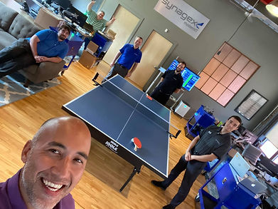 Synagex team photo showing their office lounge with ping pong table