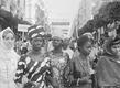 Image extraite du film Alger Festival Panafricain 1969. Des femmes en costumes traditionnels africains défilent dans la rue.