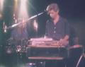Image extraite du film concert de The Del-Byzanteens avec Jim Jarmush de Georges Rey. Jim Jarmush en concert devant un synthétiseur avec un autre un autre muscien à côté de lui, dans une image floue.