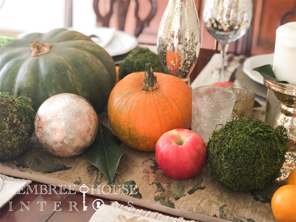 easy table runner ideas using pumpkins, apples, moss balls and magnolia leaves for decorating for the holidays