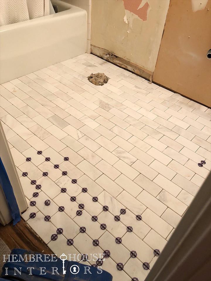 "6"" x 3"" tumbled marble tile in subway pattern laid onto bathroom floor"