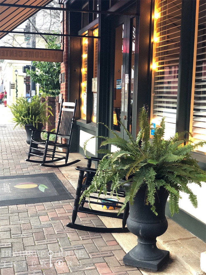 black rocking chairs outside Madison Georgia Welcome Center with ferns and rocking chairs