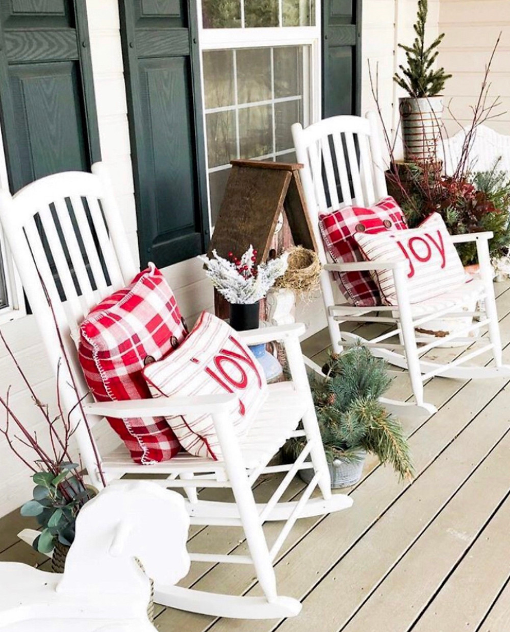 white rocking chairs on porch with christmas pillows and branches and christmas trees in containers