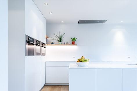 Ontwerp witte keuken waarbij de decoratie zorgt voor kleuraccenten.