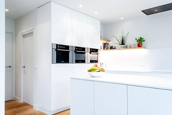 Decoratie zorgt voor kleuraccenten in de witte keuken.