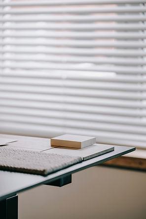 Stalen op bureau en lamellengordijn voor het raam.