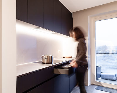 Ontwerp zwarte keuken met witte spatwand.