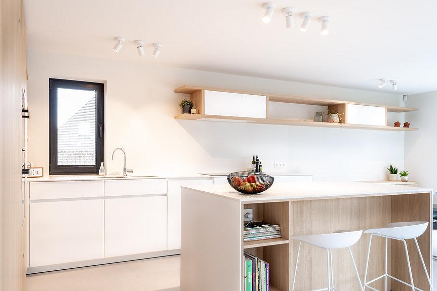 Een luchtige en frisse keuken, in verschillende tinten wit gecombineerd met hout voor een strakke maar gezellige sfeer.