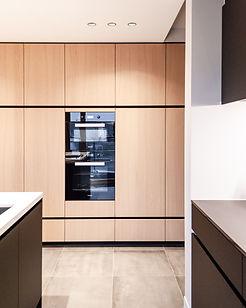 Zicht op keukentoestellen in houten kolomkasten met zwarte greeplijst.