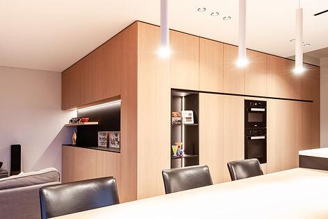 Maatwerk appartement: de keukenkasten lopen over in kasten in de zithoek. Hierdoor lijkt de ruimte groter dan ze is.