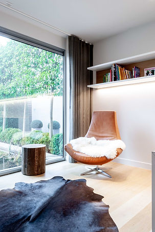 In het bureau is een zithoek voorzien, de kleur van de zetel komt terug in het hout aan de muur en geeft de ruimte een warm gevoel.