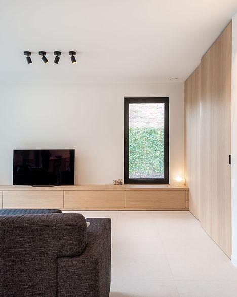 Ontwerp woonkamer. De muur en schuifdeur naar het thuiskantoor in hout vergroten het ruimtegevoel.