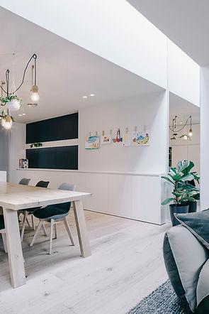 Verbouwing en inrichting rijwoning. De lichtstraat met spiegel onder en het hoogteverschil in de plafonds zorgt voor een visuele scheiding tussen eetkamer en woonkamer.