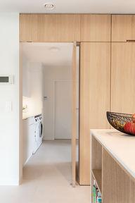 In de kolomkasten van de keuken zit een deur verborgen naar de wasplaats.