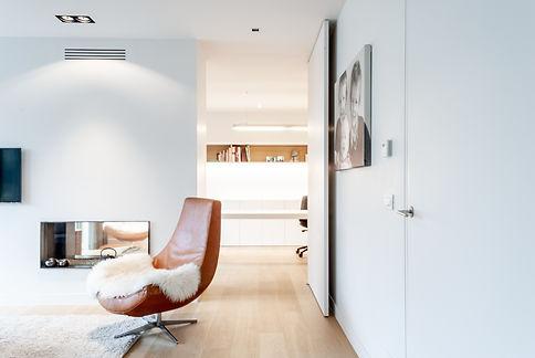 Herinrichting woning. De kleur van de zetel komt terug in het hout van de legplank aan de muur.