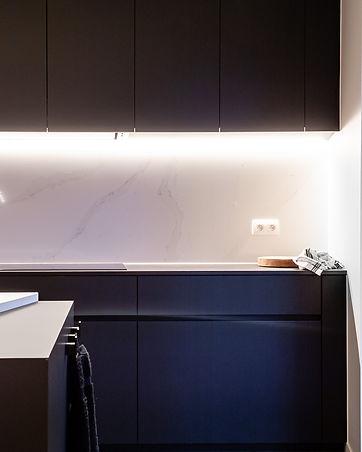 Detail zwarte keuken met spatwand in marmer-imitatie.