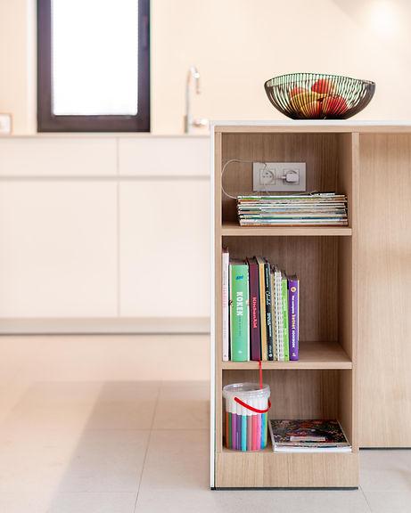 Detail keukeneiland. Een boekenkastje brengt gezelligheid in de keuken.
