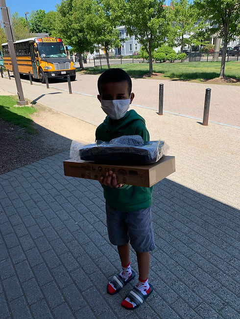 A young boy wearing a mask holding his new chromebooks