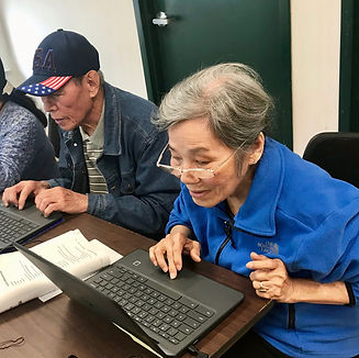 A man and a woman work on their Chromebooks
