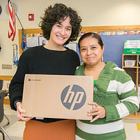 A Tech Goes Home instructor and learner smiling and holding a Chromebook together