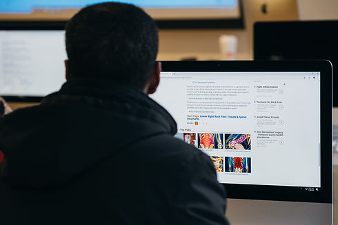 A man looks at a computer screen displaying search results about back pain