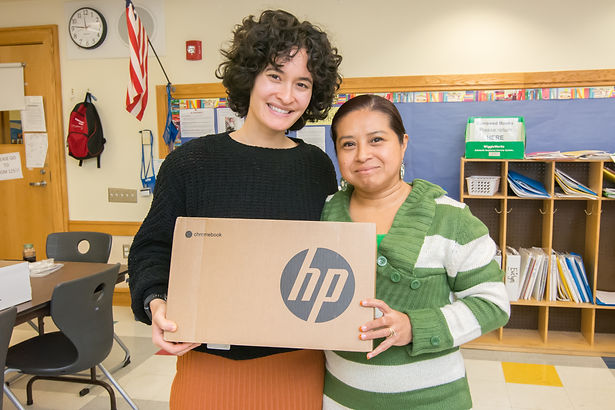 A Tech Goes Home learner and instructor smiling and holding a new Chromebook
