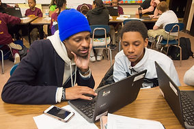 A young student and his caregiver work together on a Chromebook