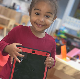 A preschool-aged child smiles holidng an iPad