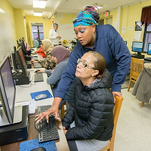 A Tech Goes Home instructor helps a learner type on her Chromebook