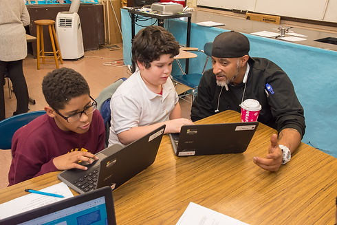 Two young students and an adult work on their chromebooks during a tech goes home course