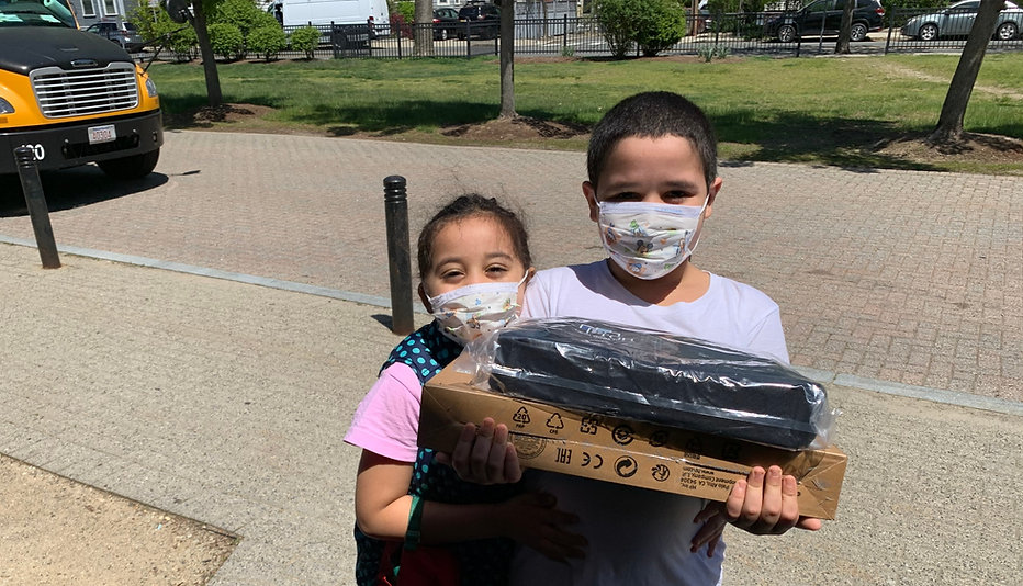 Two young children wearing masks holding their Tech Goes Home Chromebook