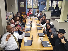 A class of tech goes home learners sitting around a conference table smiling with their chromebooks