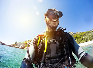 Smiling scuba diver portrait at the sea