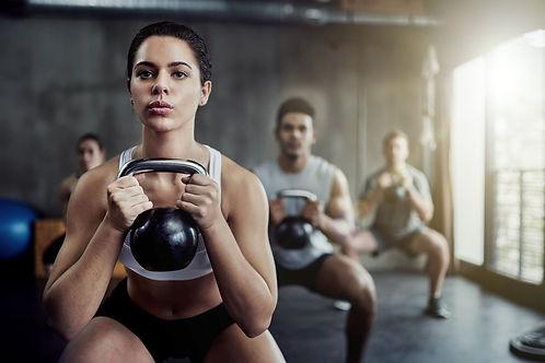 fitness class holding kettle bells